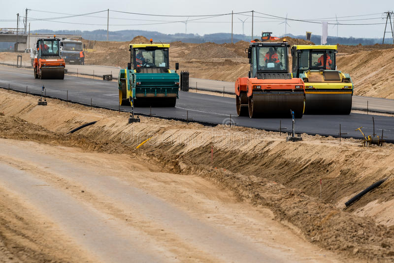 New road construction. Road rollers building the new asphalt road stock photos