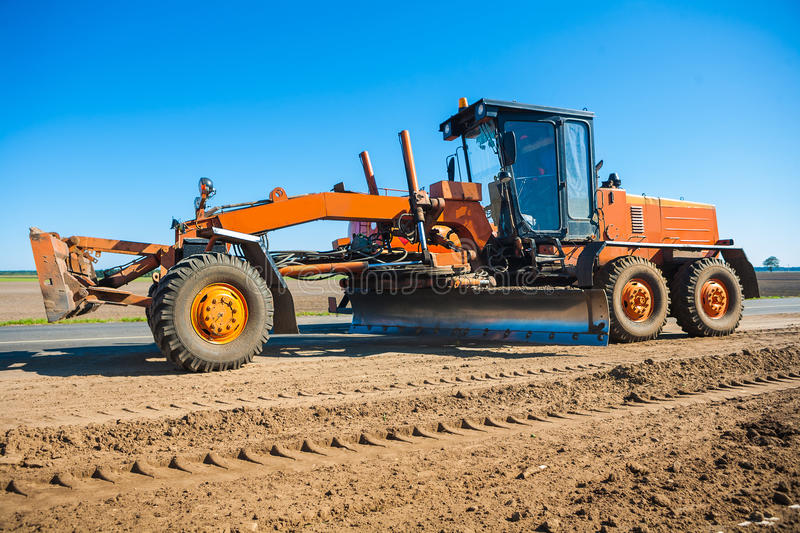 New roadworking tractor standing on edge of road stock photography