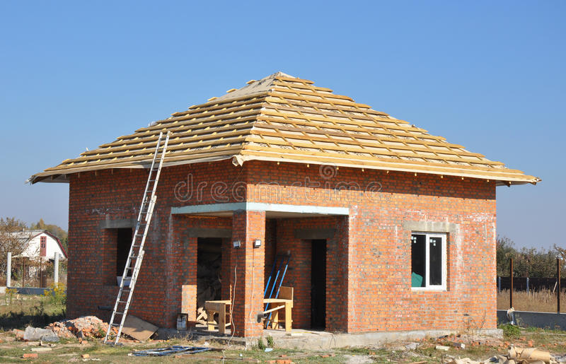 New Roof Membrane Coverings Wooden Construction Home Framing with Roof Rafters and Metal Ladder Outdoor against a Blue Sky. stock photos
