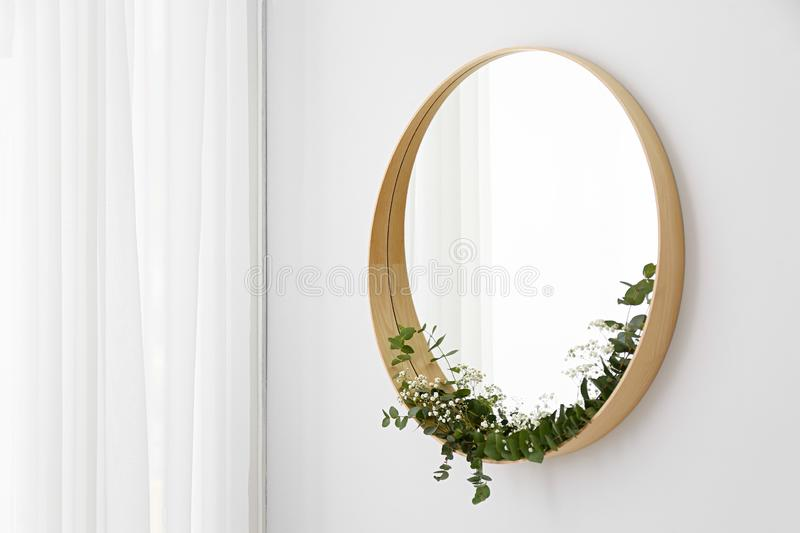 New round mirror in wooden frame on white wall. Idea for interior design stock photography