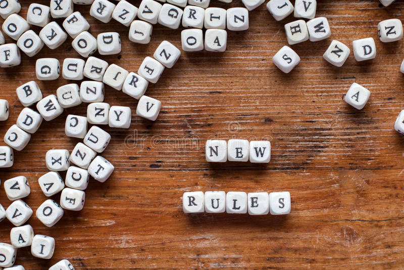 New rules. Concept, letters on wooden desk royalty free stock photo