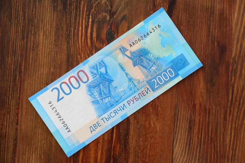 A new Russian banknote with a face value of 2000 rubles against a background of a wooden texture stock images