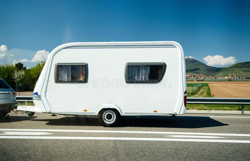 New RV trailer motorhome carried on French highway. New RV trailer motorhome carried by a gray car on French highway travel towar great holidays with clear sky royalty free stock images