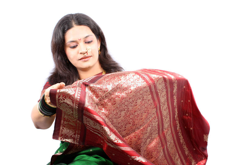 New Sari. A beautiful Indian woman checking the design on her new traditional sari, on white studio background royalty free stock image