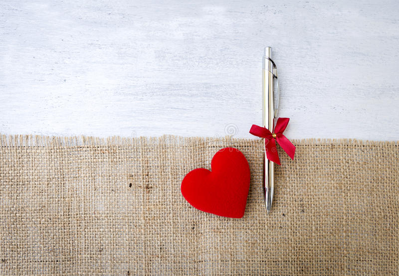New silver pen gift and red heart on hessian fabric over white wood background. Valentine`s concept royalty free stock photography