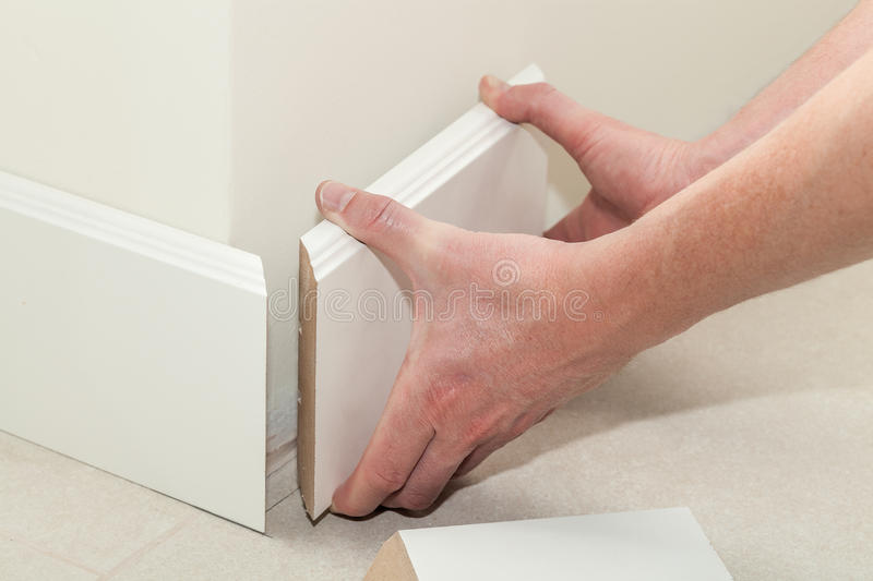 New skirting board. Man putting new skirting board in house royalty free stock photo