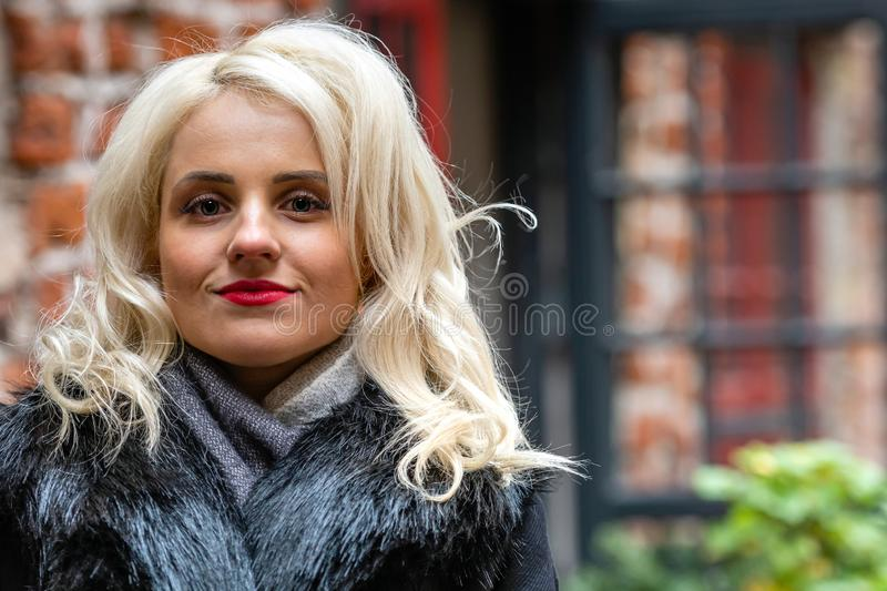 New, smiling, blond woman`s portrait on the defocused red brick building in the background stock photos