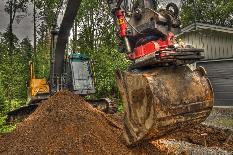 New soil for home garden in HDR. An excavator working near a new private house, levelling the new soil brought in for the garden. In HDR stock photos