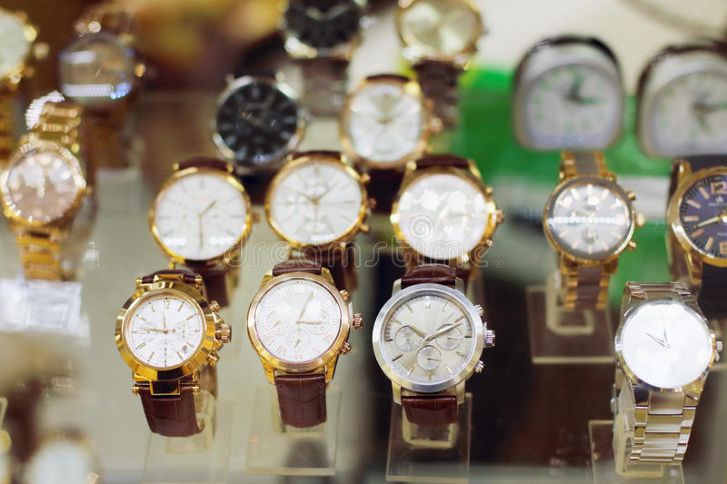 New stylish modern wristwatches in glass showcase. In shopping center stock photography