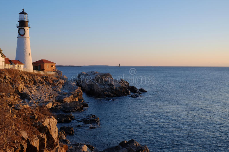The new sunrise makes the rocks glow red at the Portland Head Li stock photography