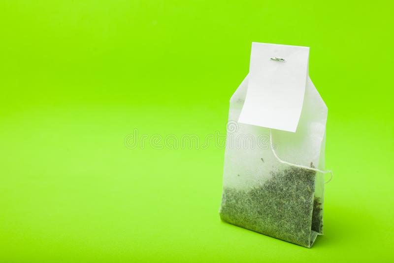 A new tea bag on a green background. Copy space, mockup stock image