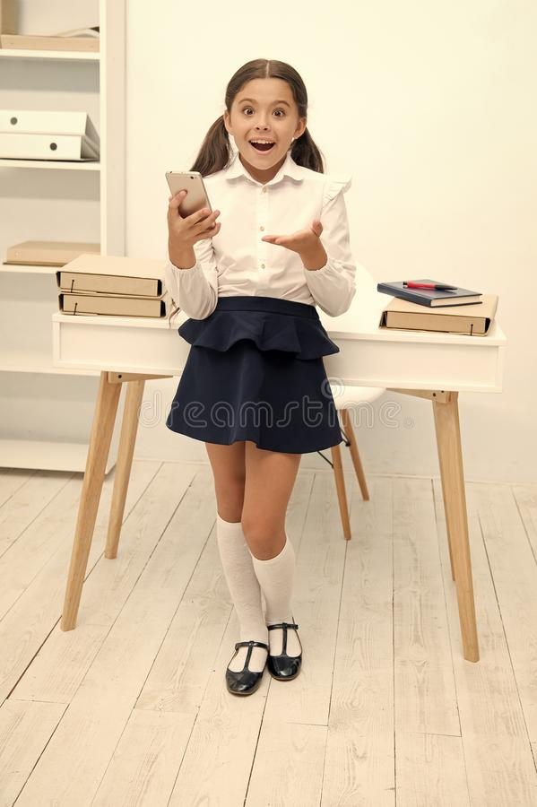 New technology concept. Learning with new technology. Little girl use smartphone on lesson, new technology. New. Technology for modern school royalty free stock photo