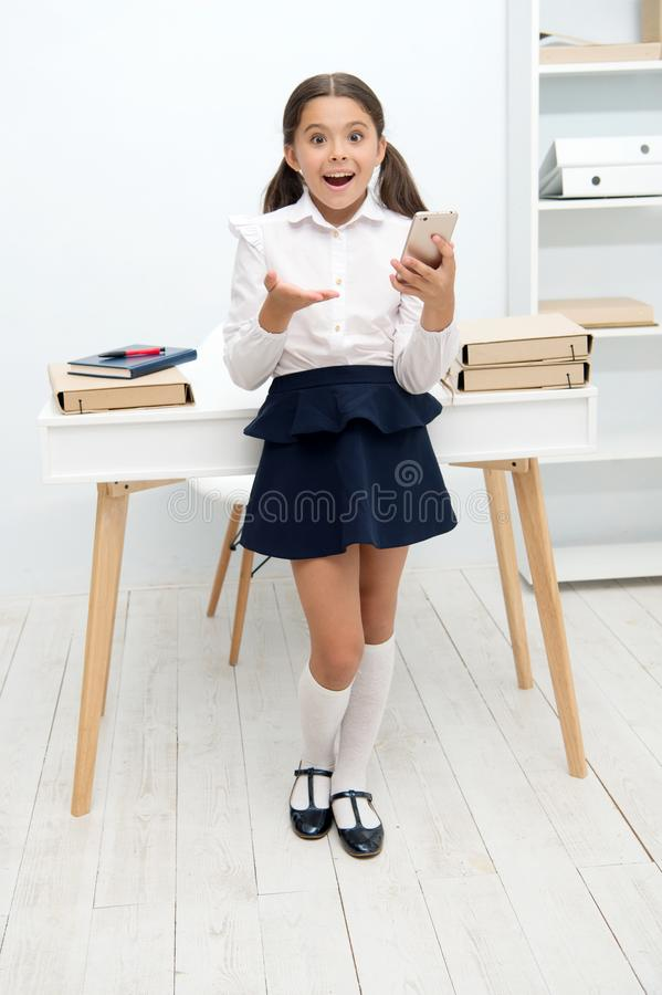 New technology concept. Learning with new technology. Little girl use smartphone on lesson, new technology. New. Technology for modern school royalty free stock image