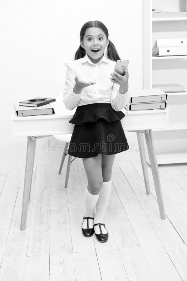 New technology concept. Learning with new technology. Little girl use smartphone on lesson, new technology. New. Technology for modern school stock photography