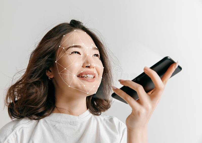 New technology of face recognition on polygonal grid. New life is coming. A woman with a smartphone in white shirt standing on white studio background. New royalty free stock images