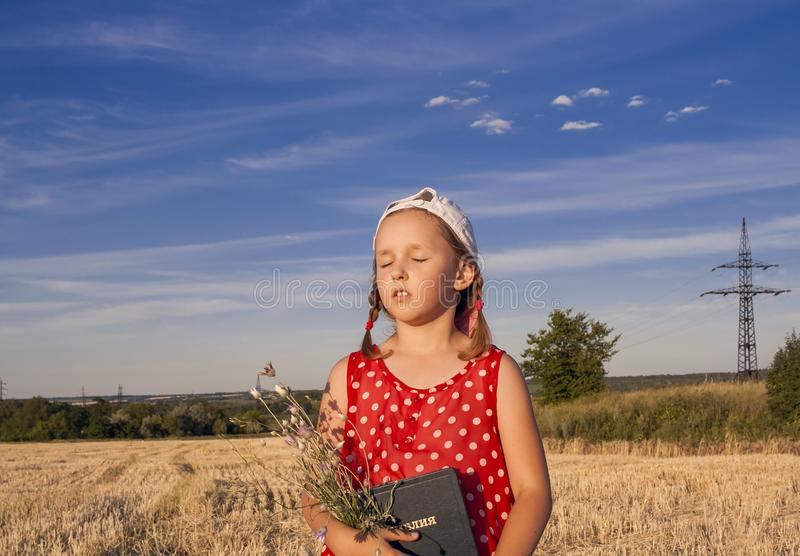 New Testament Psalms . Little girl is reading the Bible . Spiritual education . the prayer book in the child`s hands . Religion background . sacred book royalty free stock photo