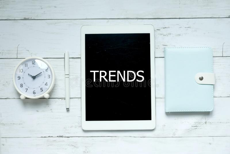 New trends technology business concept. Top view of clock,pen,notebook and tablet written with Trends on white wooden background. stock images