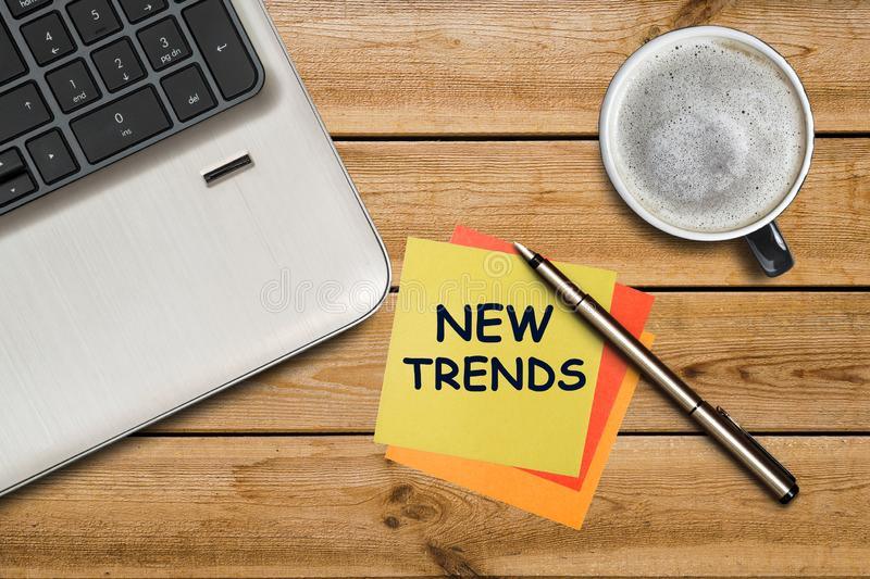 New trends written on a yellow sticker lying on a wooden table. New Trends of business concept for new year.  stock photos