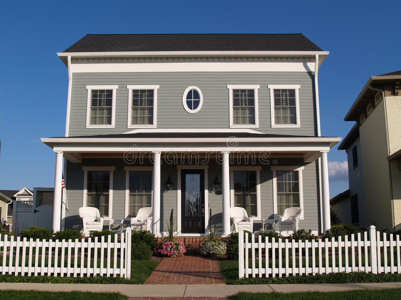 New Two Story Vinyl Home With Historical Look. New two story vinyl home built to look like an old historical house with gray vinyl siding and large front porch stock photos