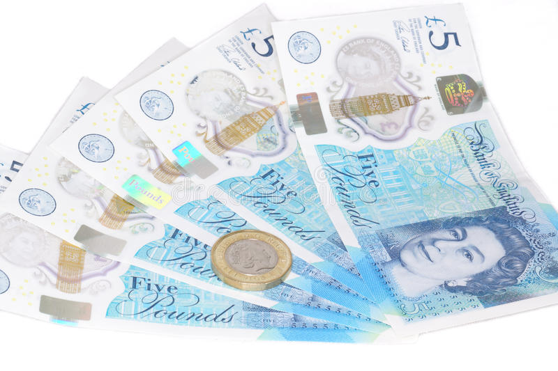 The new UK polymer five pound note and the new 12 sided £1 coin. The newly introduced currency of the United Kingdom - The polymer five pound £5 note with royalty free stock photo