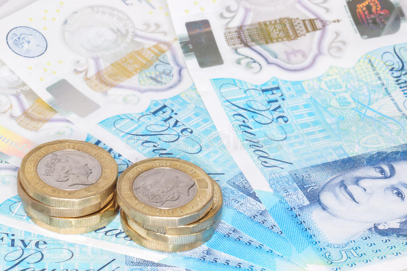 The new UK polymer five pound note and the new 12 sided £1 coin. The newly introduced currency of the United Kingdom - The polymer five pound & x28;£5& x29 stock photography