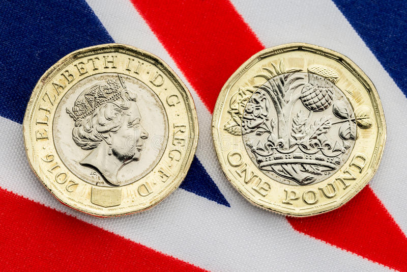 New UK pound coin detail of heads and tails. New British pound coin showing heads and tails on a Union Jack flag background. Close up detail of the bimetallic stock photography