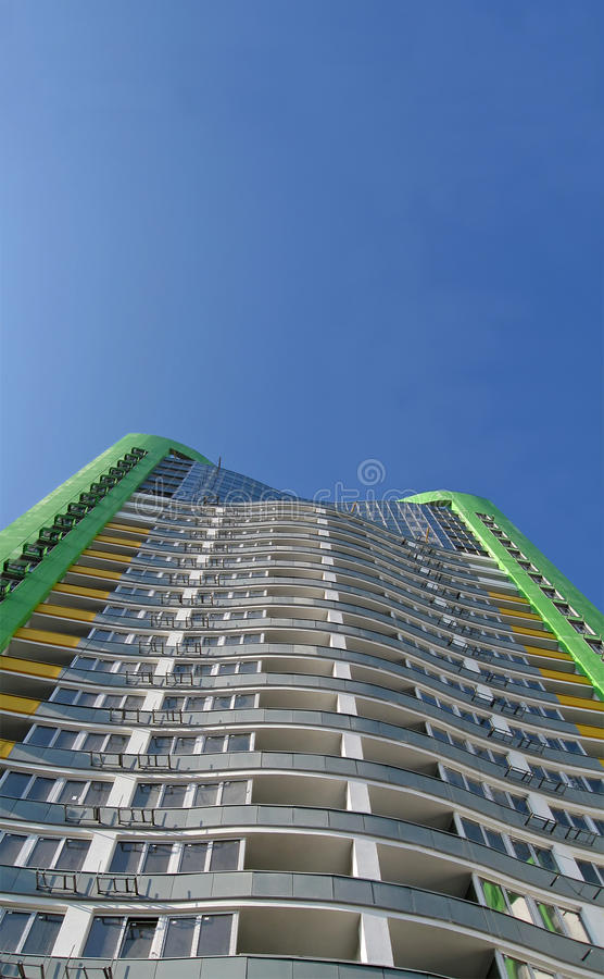 New urban high building, green color, blue sky. Skyscraper (green color), urban building with many windows. Construction of new buildings (commercial real estate royalty free stock images