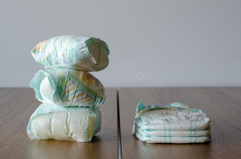 New and used baby diapers on the wooden table background. royalty free stock images