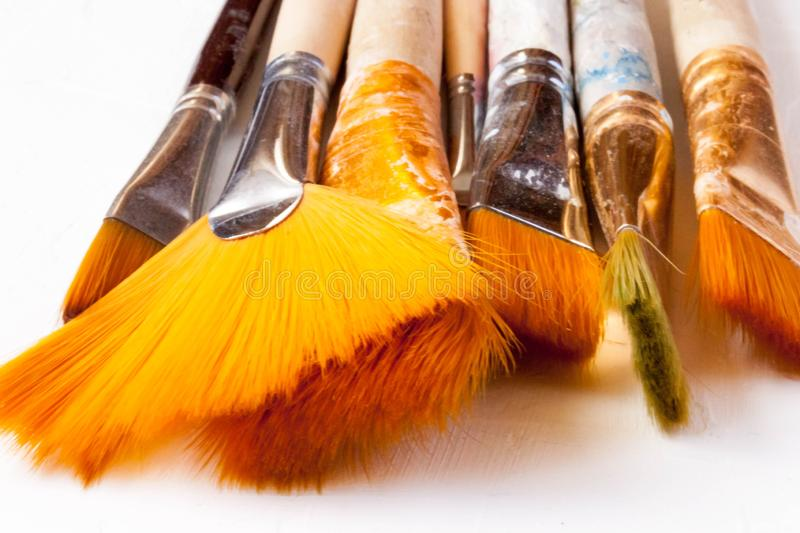 New and used bunch of paint brush on background. New and used bunch of paint brush on light white background. Selective soft fokus. Text copy space stock photo
