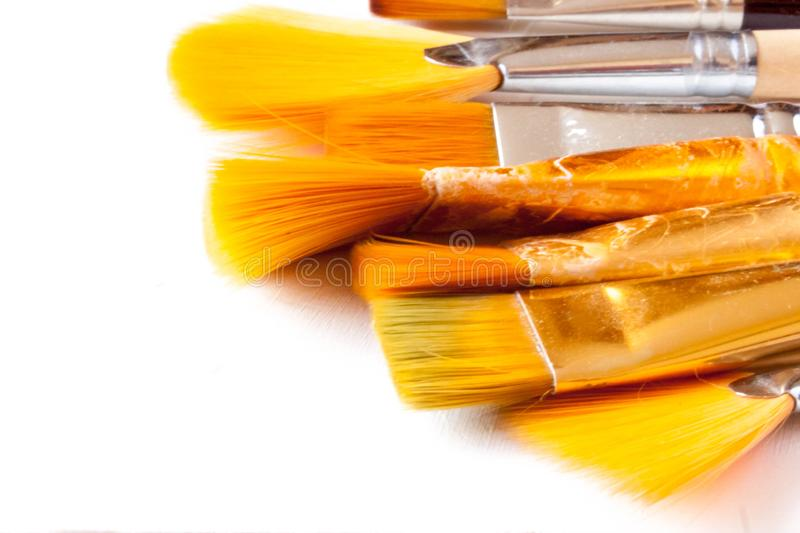 New and used bunch of paint brush on background. New and used bunch of paint brush on light white background. Selective soft fokus. Text copy space stock photos