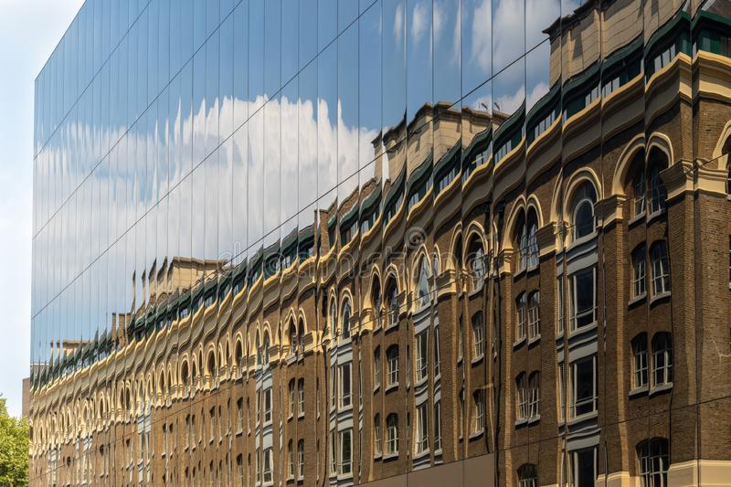 New versus old - an old brick building reflected in windows of m stock photography