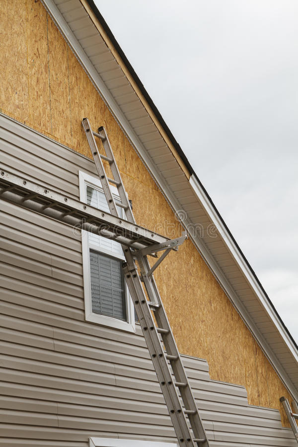 New Vinyl Siding Installation On A Home In The South. New beige vinyl siding being installed over an osb (oriented strand board) substrate on a residential house stock photos
