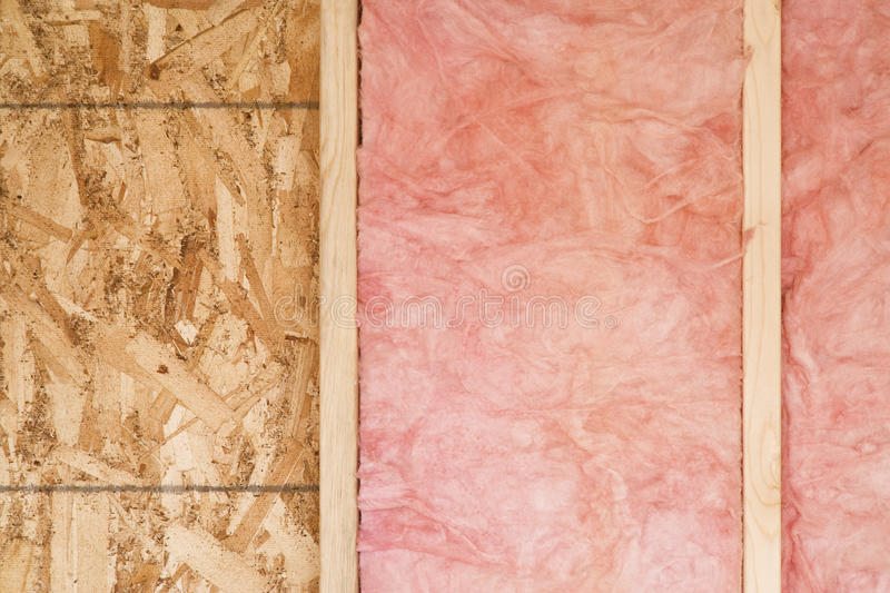 New Wall With Fiberglass Insulation. Close-up of strips of pink fiberglass insulation in a wall of a new building. Horizontal shot royalty free stock photos