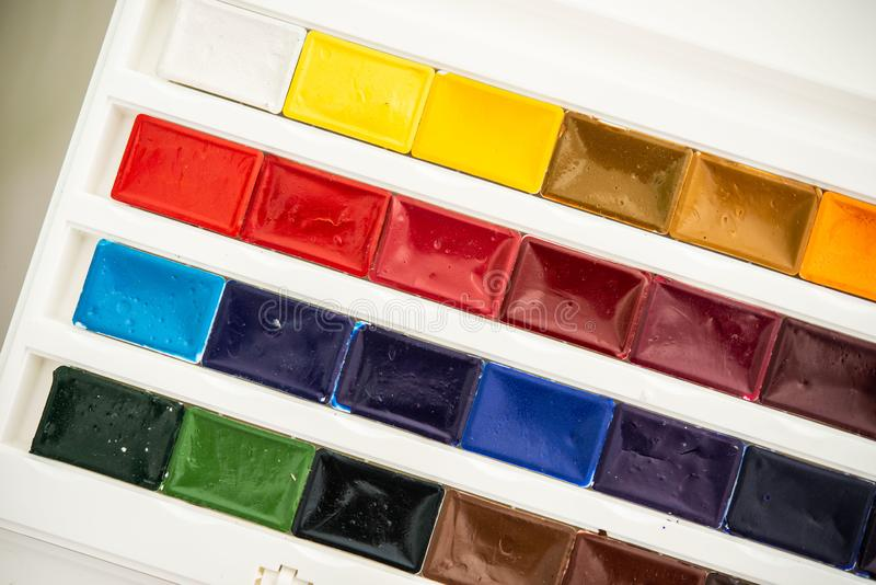 New watercolor paints  in cuvettes in a white plastic box with a palette royalty free stock photo
