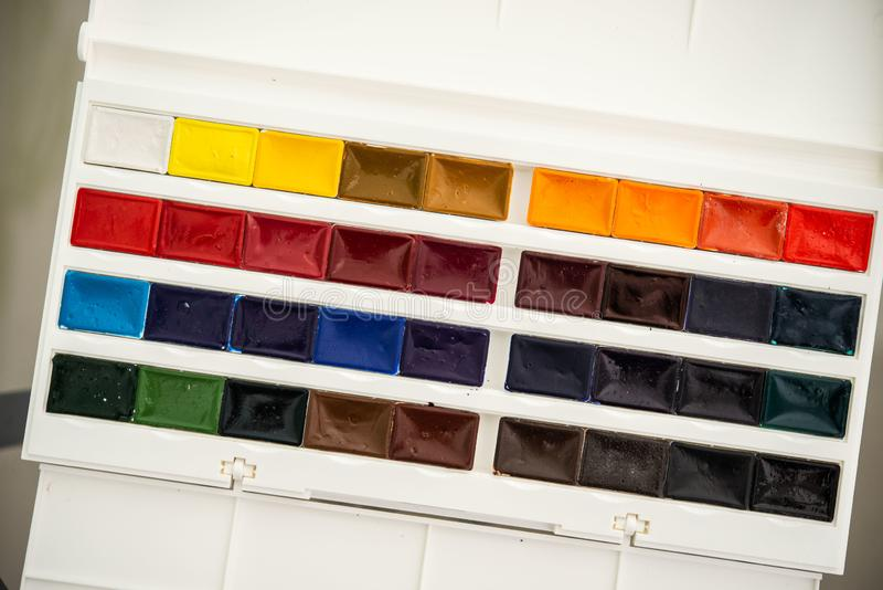 New watercolor paints  in cuvettes in a white plastic box with a palette stock photos