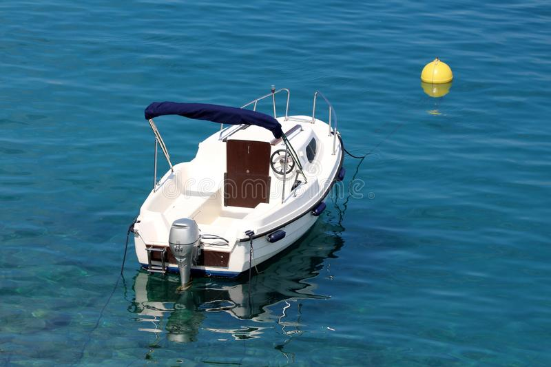 New white boat with outboard boat motor tied in local harbor to bright yellow buoy surrounded with calm clear blue sea. On warm sunny day stock photos
