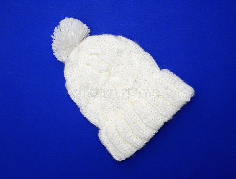 New White / Cream Wool Knit Hat. New White /Cream Wool Knit Hat with Pom Pom on blue background royalty free stock image