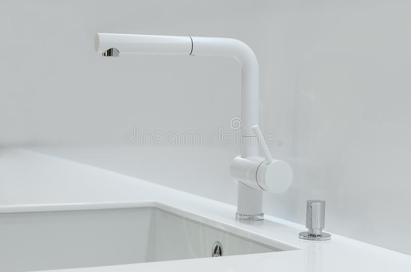 A new white kitchen sink made of artificial stone and a faucet. The concept of modern kitchen interior. Close-up royalty free stock photo