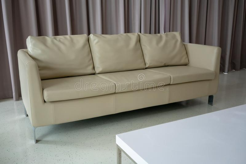 New white leather couch on white floor against light brown curtain. royalty free stock photography
