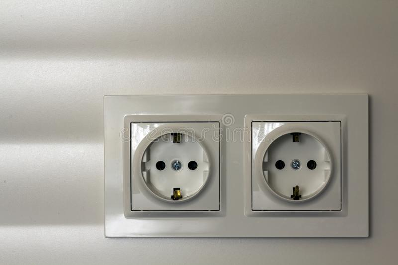 New white shiny plastic electric double sockets on white wall background. Advantages and comfort of modern homes. New white shiny plastic electric double royalty free stock images