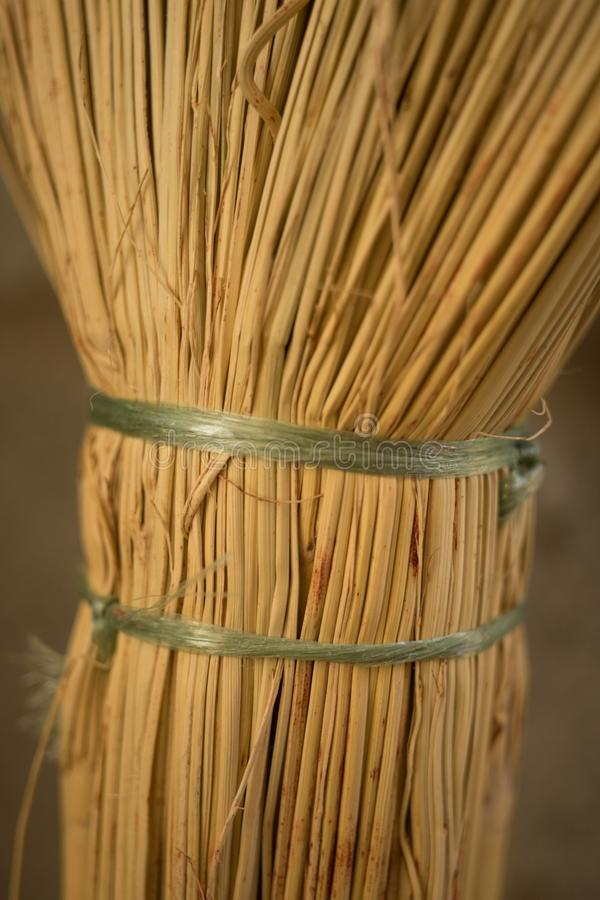 New wicker broom handle closeup with green ropes.  royalty free stock images
