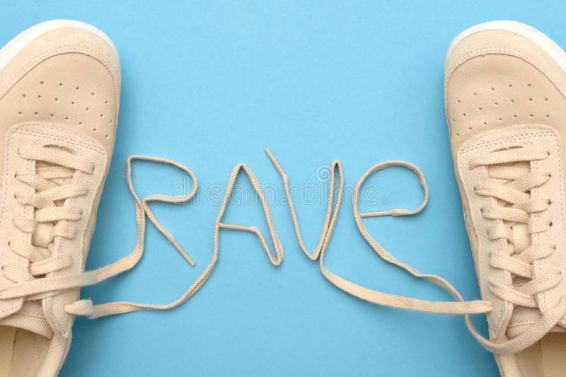 New women sneakers with laces in rave text. Flat lay on blue background stock images