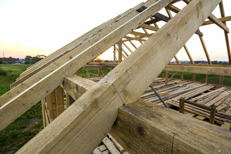 New wooden ecological house from natural materials under construction. Close-up detail of attic roof frame against clear sky from stock photo