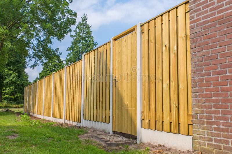 New wooden fence construction with brick wall stock image