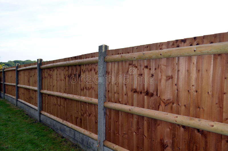 New wooden fence. Wooden slat fencing with concrete posts surrounding an urban garden royalty free stock photography