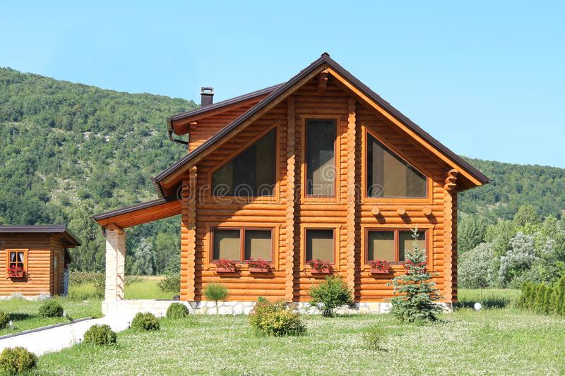 New wooden log cabin house surrounded with grass and forest stock images