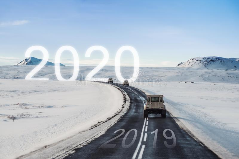 New year and new achievements concept. Group of car driving on the road heading to 2020 with 2019 on the road. New year and new achievements concepts. Group of stock photos