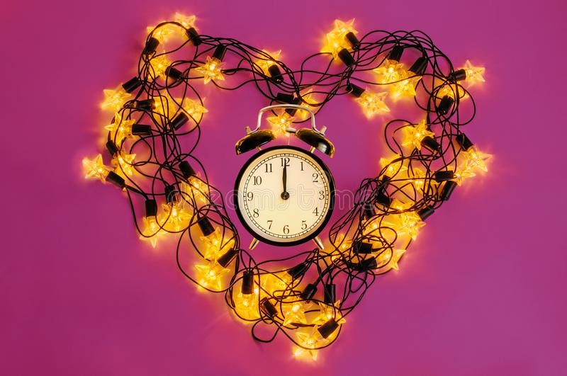 New Year alarm clock inside of a heart created of led garland on a pink background. royalty free stock photos