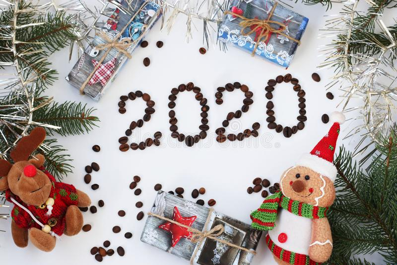 New Year background with a Christmas tree, garland, gifts and toys, The inscription 2020 made of coffee beans stock photos