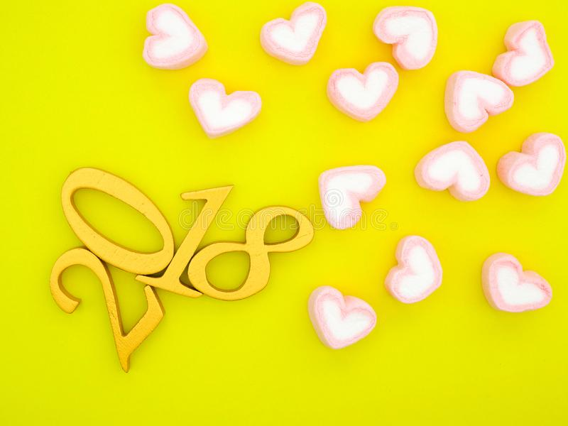 New Year 2018 Banner. A new year 2018 banner in gold with pink heart shape marshmallow on bright lemon yellow background royalty free stock image